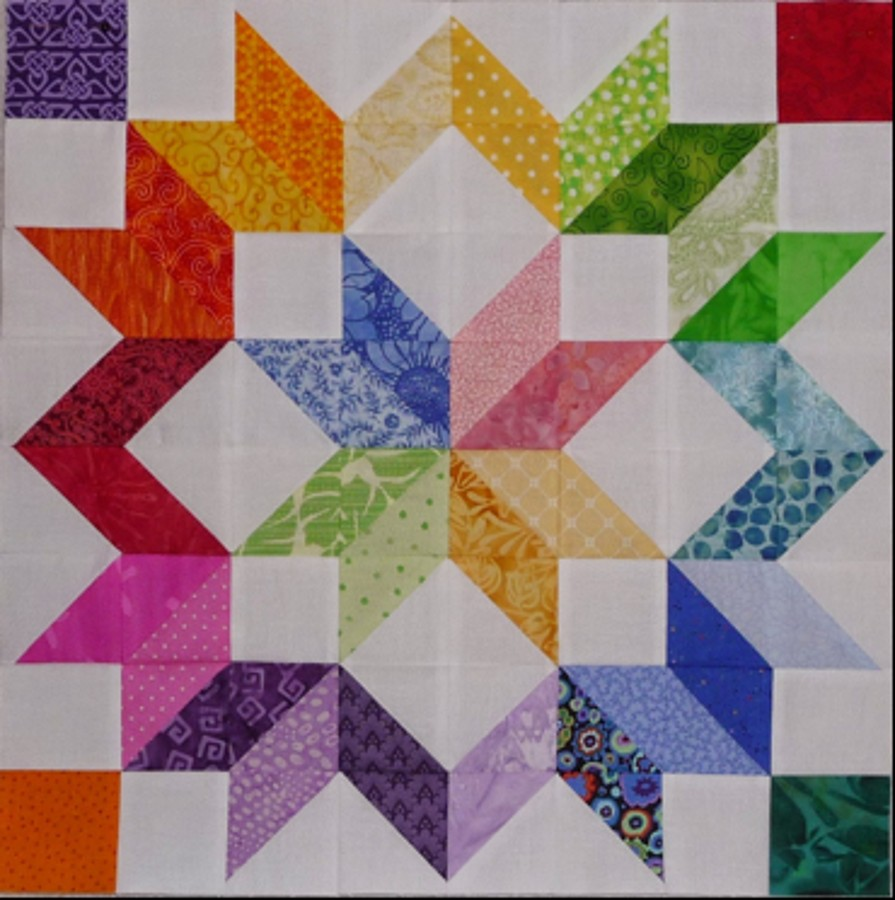 A brightly colored Carpenter's Wheel quilt block.