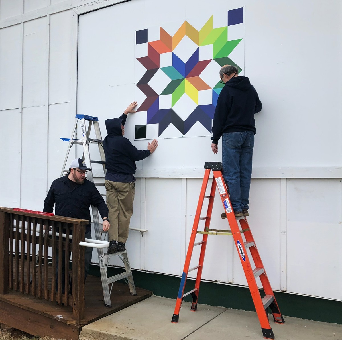 Parks & Rec Staff installing the Carpenter's Wheel Quilt Square at Franklin Park Arts Center in Purcellville.
